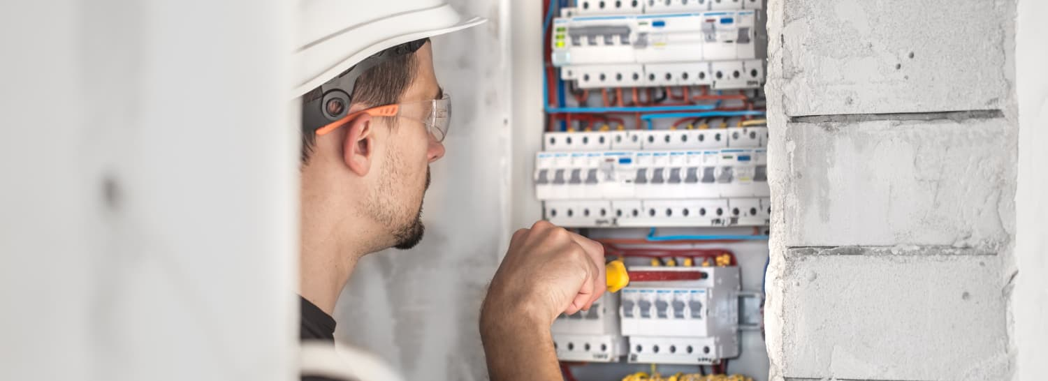 man-electrical-technician-working-switchboard-with-fuses-installation-connection-electrical-equipment
